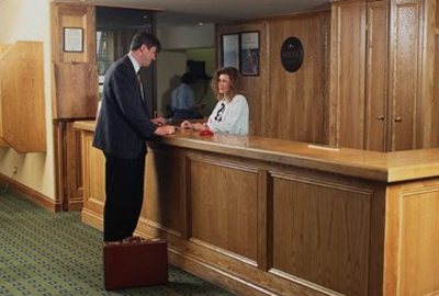 Front desk agent greets hotel guest in training video.